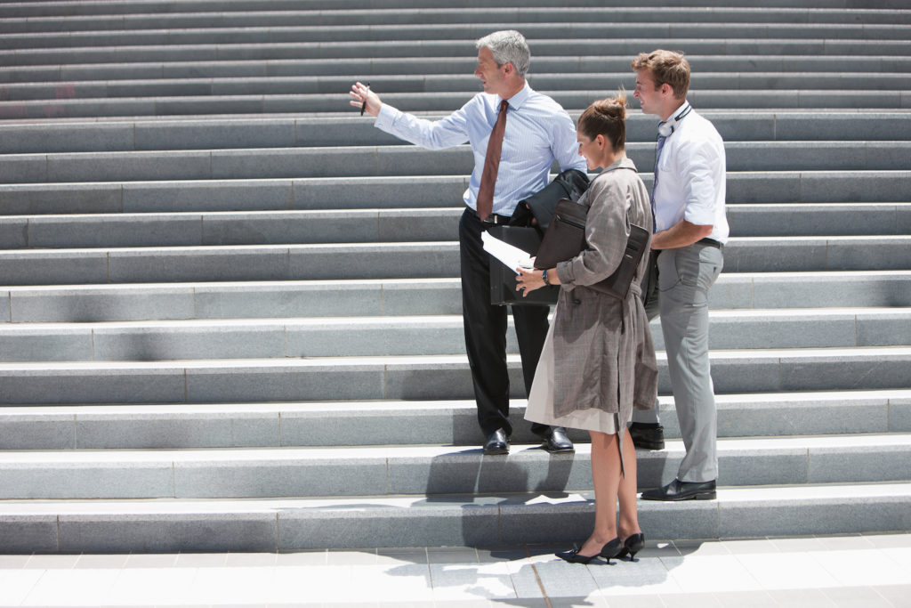 Photo of people looking up stairs and getting ready to go